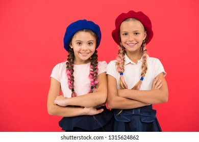 Stylish and confident. Cute girls having the same hairstyle. French style girls. Small children with long hair plaits. Fashion girls with tied hair into braids. Little kids wearing french berets.