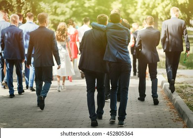 stylish confident man in suit having fun, group of people walking, reception at luxury wedding, rich graduation at school or university