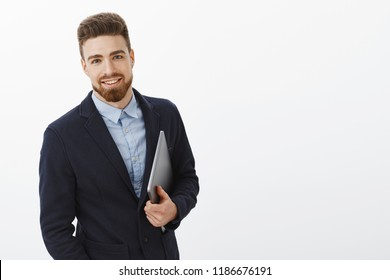 Stylish confident and sexy male entrepreneur with blue eyes and beard standing self-assured in formal suit holding laptop in hand gazing pleased and assured at camera, being ambitious and successful