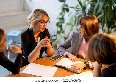 Stylish confidently looking female owner of small fashion agency showing good statistics report explaining deal advantages convincing her female partners at meeting at office.
