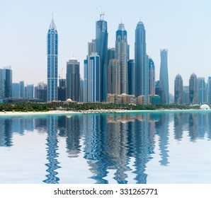 Stylish and contemporary architecture of a modern, metropolitan skyline, towering over a tropical beach and reflecting in a calm sea.