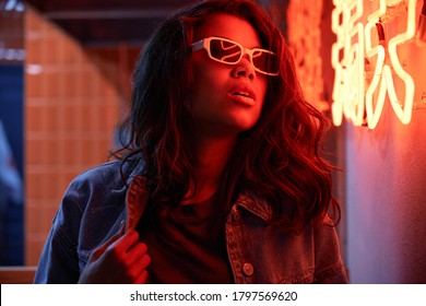 Stylish cool fashion funky African American young beautiful hipster girl mixed race model wears trendy glasses posing near red neon sign in night club. 80s 90s gen z retro style party nightclub event.
