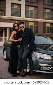 Stylish couple in black posing against the backdrop of a business class car. Fashion.