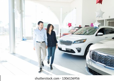 Stylish couple choosing new automobile while walking by luxury cars in car dealership