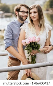 Stylish couple in embrance on quay with nature background. Girl in white dress with fresh flowers holds hand of man