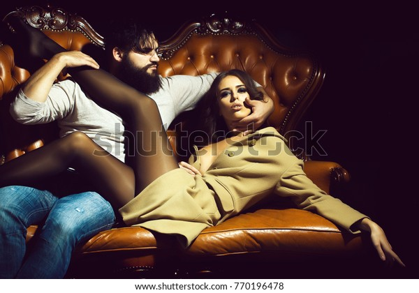 Stylish couple of handsome bearded man and young sexy woman sitting on leather sofa