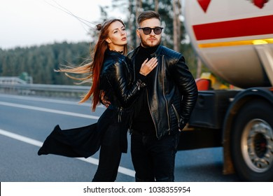 stylish couple in leather clothes hugs on the road among cars