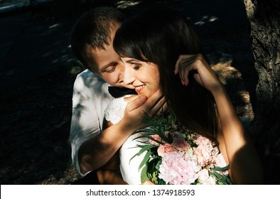 stylish couple in love - the bride and groom - on a walk on their wedding day in the park, gently hugging and smiling