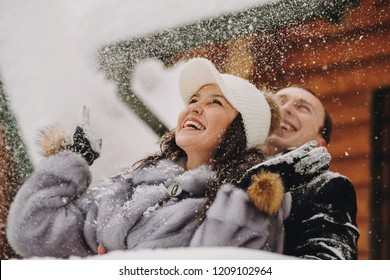 Stylish couple playing with snow in wooden cabin on background of winter snowy mountains. Happy joyful family having fun and smiling in snow. Emotional funny moments together