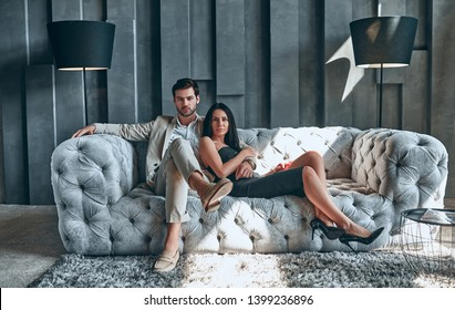 Stylish couple sitting on sofa together. Handsome bearded man in suit and attractive woman in black dress at home.