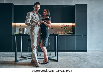 Stylish couple standing on modern kitchen and drinking champagne together. Handsome bearded man in suit and attractive woman in black dress at home.