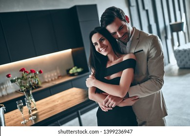 Stylish couple standing on modern kitchen together. Handsome bearded man in suit and attractive woman in black dress at home.