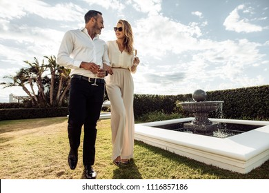 Stylish couple walking outdoors in lawn with a glass of wine. Man and woman looking at each other and walking together outdoors..