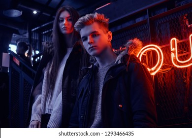 Stylish couple wearing warm clothes standing in the cafe with industrial interior, a backlit signboard in the background