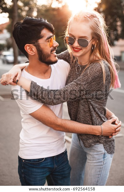 Stylish couple is whirling on the street under the sunlight.