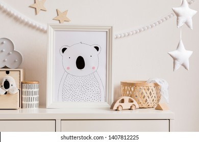 Stylish and cozy childroom with white mock up photo frame, wooden accessories, toys, clouds, rattan basket and white garland and stars on the white wall. Bright and sunny interior. Template,