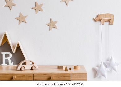 Stylish and cozy childroom with wooden accessories, toys, mountain box, car, basket and stars pattern on the background wall. Bright and sunny interior. Template, Copy space for inscription, products.