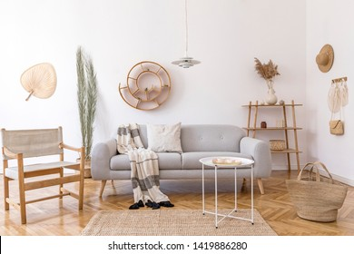 Stylish and cozy interior of living room with elegant rattan accessories, design armchair, gray sofa and wooden shelf. Korean style of home decor. Hanging rattan snail with airplants.
