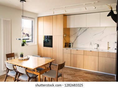Stylish and cozy scandinavian dining  and kitchen interior with design family table, chairs and lamp. White marble walls and brown wooden parquet.