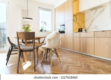 Stylish and cozy scandinavian dining room and kitchen with design family table, chairs and lamp. White and marble walls  and brown wooden parquet. Bright and sunny interior.