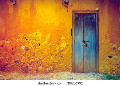 Stylish cracked vintage colorful wall in yellow orange shades with royal blue wooden door. Ideal background for retro style illustrations and collages. Grunge style. Artistic retouching.