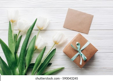 stylish craft present box and greeting card and tulips on white wooden rustic background. flat lay with flowers empty paper with space for text. hello spring concept. holiday gift