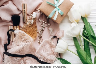 stylish craft present box and lace lingerie jewelry and perfume present on soft fabric and tulips on white rustic background. flat lay woman essentials for a holiday. instagram photo