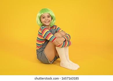 Stylish and creative. Happy child wear stylish short hair wig yellow background. Little girl smile with stylish look. Stylish hair salon. Fashion and style.