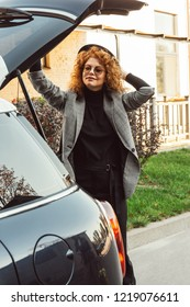 stylish curly redhead woman in grey jacket closing car trunk at city street