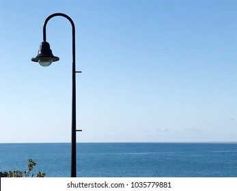 Stylish curved decorative lamp post with ocean background, Kings Beach Australia