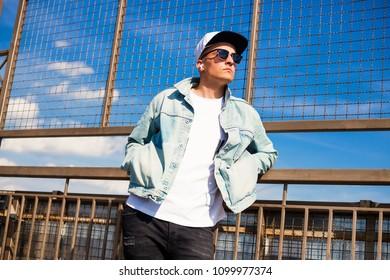 Stylish cute guy is standing on the bridge, wearing a denim jacket cap, listening to music through headphones free hands