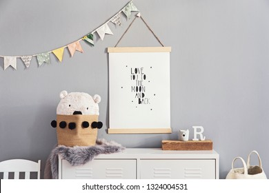 Stylish and cute scandinavian decor of  kid room with mock up poster, white shelf, natural toys, hanging decor flags , child's armchair, basket for accessories and teddy bears. Minimalistic concept.
