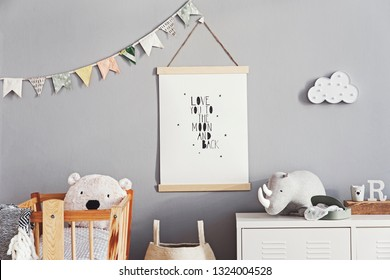 Stylish and cute scandinavian decor of  newborn baby room with mock up poster, natural toys, hanging decor flags and cloud, wooden cradle, basket for accessories and teddy bears. Grey walls .