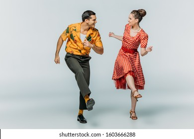 stylish dancers looking at each other while dancing boogie-woogie on grey background