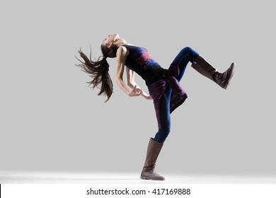 Stylish dancing young woman portrait. Fit sporty girl wearing English flag tank top warming up, working out with her long ponytail flying. Studio image. Grey background. Full length