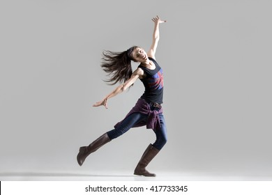 Stylish dancing young woman portrait. Fit girl wearing English flag tank top warming up, working out. Happy dancer spinning on one leg with her ponytail flying. Studio image. Grey background