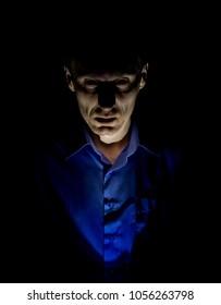 Stylish dark portrait of adult caucasian man who seems like maniac or psycho. Isolated on black background. Low-key lighting.