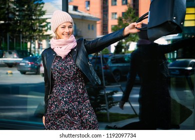 Stylish darkhaired woman wearing black jacket, dress and knitting hat  fun waving a bag and enjoys a new day on the background mirrow wall at the street big city.