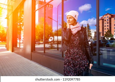 Stylish darkhaired woman wearing black jacket, dress and knitting hat  smiling, go to work and look to away day on the background mirrow wall at the street big city.