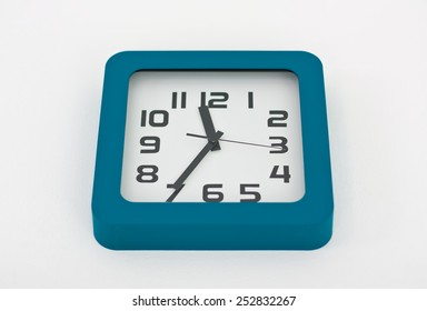 A stylish decorative wall clock hanging from a white wall.