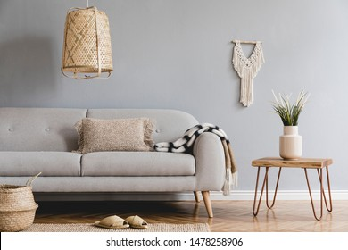 Stylish and design home interior of living room with gray sofa, wooden coffee table , pillows, blankets, rattan lamp, macrame, flowers, basket and elegant accessories. Stylish home decor. Template.
