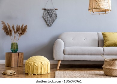 Stylish and design home interior of living room with gray sofa, wooden cube, flowers, pillow, macrame, yellow pouf, rattan lamp, basket, plants and elegant accessories. Stylish home decor. Template.