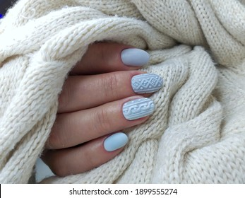 stylish design of manicure on nails in the style of minimalism. Blue-gray shade of gel polish for short nails. Winter design on a matte top on nails .Knitting