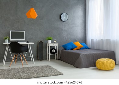 Stylish designed boy teenager's bedroom with grey walls and white furniture and colorful decorations