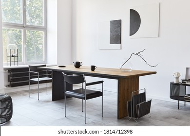 Stylish dining room interior with design wooden family table, black chairs, teapot with mug, mock up art paintings on the wall and elegant accessories in modern home decor. Template.