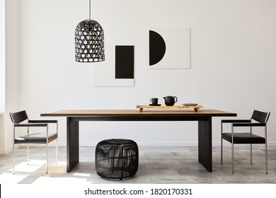 Stylish dining room interior with design wooden family table, black chairs, teapot with mug, mock up art paintings on the wall and elegant accessories in modern home decor. Template. - Shutterstock ID 1820170331