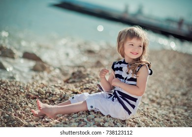 Stylish dressed blond child girl enjoy posing summer vacation on public city beach wearing casual bright clothes happy smiling on camera alone.