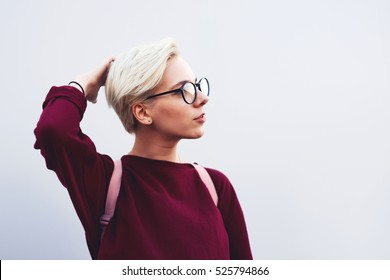 Stylish dressed female hipster traveler looking to the side with copy space area for your advertising text message or promotional content. Young woman in trendy eye glasses with mock up wear