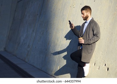 Stylish dressed hipster guy standing in the evening outdoors and using mobile phone application while chatting with friends. Young male in trendy coat browsing internet on smartphone in urban setting