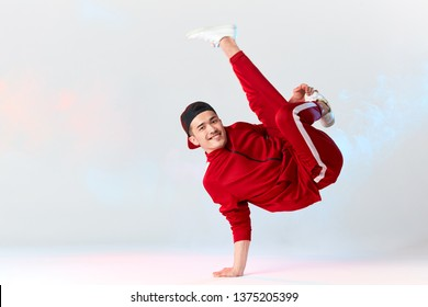 Stylish dressed in red sweatpants asian b-boy is performing kick in air, standing on hands while dancing break dance on white background. Freestyler doing air baby freeze